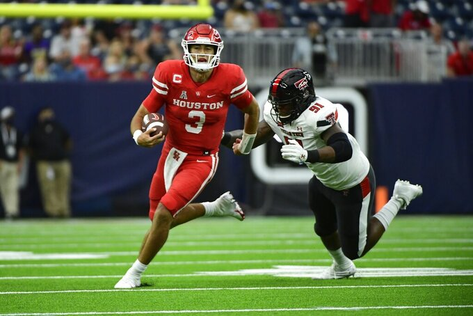 Houston quarterback Clayton Tune (3) runs the ball against Texas Tech defensive lineman Nelson Mbanasor (91) during the first half of an NCAA college football game Saturday, Sept. 4, 2021, in Houston. (AP Photo/Justin Rex)