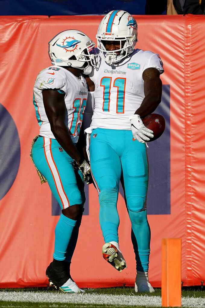 Miami Dolphins wide receiver DeVante Parker (11) celebrates his touchdown catch with wide receiver Jakeem Grant (19) during the first half of an NFL football game against the Denver Broncos, Sunday, Nov. 22, 2020, in Denver. (AP Photo/Jack Dempsey)
