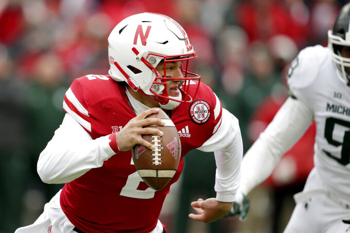 Nebraska quarterback Adrian Martinez (2) scrambles away from Michigan State defensive tackle Raequan Williams (99) during the first half of an NCAA college football game in Lincoln, Neb., Saturday, Nov. 17, 2018. (AP Photo/Nati Harnik)