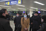 Passengers wearing masks as a precaution against a new coronavirus stand before boarding a flight to Vladivostok, Russia, at the Pyongyang International Airport in Pyongyang, North Korea, Monday, March 9, 2020. (AP Photo/Cha Song Ho)