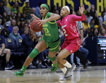 Oregon's Minyon Moore, left, drives the ball past California's Cailyn Crocker (2) during the first half of an NCAA college basketball game Friday, Feb. 21, 2020, in Berkeley, Calif. (AP Photo/Ben Margot)