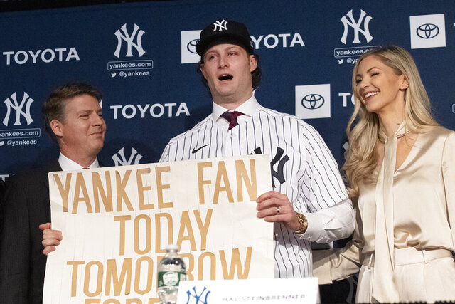 New York Yankees pitcher Gerrit Cole, center, holds a sign he used as a young Yankees fan, as he is introduced as the baseball clubs newest player during a baseball media availability, Wednesday, Dec. 18, 2019 in New York. He is joined by team owner Hal Steinbrenner, left, and his wife, Amy Cole. (AP Photo/Mark Lennihan)