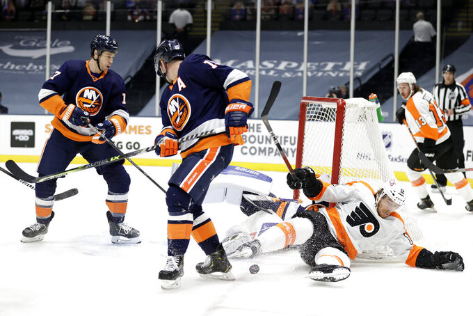 Philadelphia Flyers left wing Michael Raffl (12) slides across the ice after colliding with New York Islanders goaltender Ilya Sorokin during the first period of an NHL hockey game Saturday, March 20, 2021, in Uniondale, N.Y. (AP Photo/Adam Hunger)
