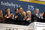 FILE - In this March 11, 2019, file photo Sotheby's Chairman Domenico De Sole, second from right, is applauded by CEO Tad Smith, right, and others as he rings the New York Stock Exchange opening bell to celebrate the company's 275th anniversary.  BidFair USA is taking auction house Sotheby's private in a deal valued at $3.7 billion. BidFair USA will pay $57 per share, which is a 61% premium to the company's closing stock price. (AP Photo/Richard Drew, File)