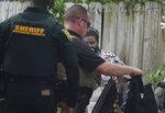 A Broward Sheriff's Office Deputy detains one of the multiple migrants who came ashore on the intracoastal waterway Thursday, June 17, 2021, in Pompano Beach, Fla. (Joe Cavaretta/South Florida Sun-Sentinel via AP)