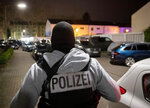 A police officer guards the road in front of a house that is searched through by police in Hanau, Germany Thursday, Feb. 20, 2020. Eight people were killed in shootings in and outside two hookah lounges in a southwestern German city late Wednesday, and authorities were searching for the perpetrators. (AP Photo/Michael Probst)