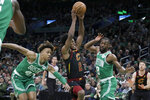 Cleveland Cavaliers guard Collin Sexton (2) drives between Boston Celtics guards Romeo Langford (45) and Kemba Walker (8) in the first half of an NBA basketball game, Friday, Dec. 27, 2019, in Boston. (AP Photo/Elise Amendola)