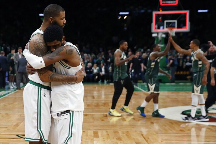 Boston Celtics' Marcus Morris, left, hugs Kyrie Irving as the Milwaukee Bucks celebrate their 123-116 win in Game 3 of a second round NBA basketball playoff series in Boston, Friday, May 3, 2019. (AP Photo/Michael Dwyer)