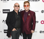 FILE - This March 25, 2017 file photo shows Elton John, right, and Bernie Taupin at Elton John's 70th Birthday and 50-Year Songwriting Partnership with Taupin in Los Angeles. The pair were nominated for a Golden Globe for best original song