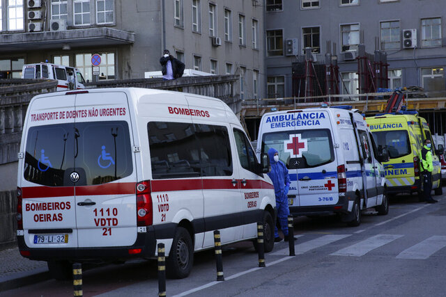 Ambulances bringing patients are parked outside the COVID-19 emergency ward at the Santa Maria hospital in Lisbon, Monday, Jan. 18, 2021. Stricter lockdown rules are being enacted in Portugal, the country's government announced Monday, as a surging COVID-19 pandemic sets grim records and pushes hospitals to the limit of their capacity. (AP Photo/Armando Franca)