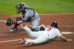 Cleveland Indians' Mike Freeman scores as Chicago White Sox catcher Yasmani Grandal waits for the throw during the seventh inning of a baseball game Thursday, Sept. 24, 2020, in Cleveland. The Indians won 5-4. (AP Photo/Tony Dejak)