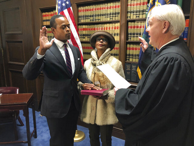 Republican Daniel Cameron is sworn in on Tuesday, Dec. 17, 2019, in Frankfort, Ky., as the first African-American in Kentucky history to serve as its attorney general. Cameron's hand is on a Bible being held by his mother, Sandra Cameron, as U.S. District Judge Gregory F. Van Tatenhove administers the oath of office. (AP Photo/Bruce Schreiner)