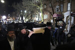 Orthodox Jewish men carry the casket with Mindel Ferencz outside a Brooklyn synagogue, Wednesday, Dec. 11, 2019, in New York. Her funeral will be in Jersey City. Ferencz was killed Tuesday in the shooting inside a Jersey City, N.J. food market. (AP Photo/Mark Lennihan)