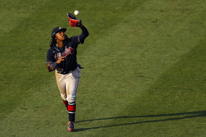 Atlanta Braves center fielder Ronald Acuna Jr. catches a fly out by Philadelphia Phillies' Bryce Harper during the fifth inning of the second baseball game in a doubleheader, Sunday, Aug. 9, 2020, in Philadelphia. (AP Photo/Matt Slocum)