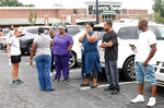 Anxious parents stand in the parking lot of a shopping center in Winston-Salem, N.C., on Wednesday, Sept. 1, 2021. One student was killed in a shooting at a North Carolina high school Wednesday and authorities were looking for the suspect, officials said. (AP Photo/Skip Foreman)