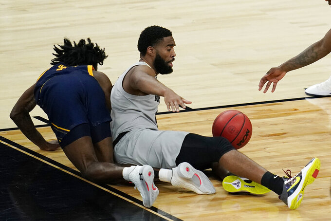 California's Joel Brown, left, and Colorado's Jeriah Horne fall to the court during the second half of an NCAA college basketball game in the quarterfinal round of the Pac-12 men's tournament Thursday, March 11, 2021, in Las Vegas. (AP Photo/John Locher)