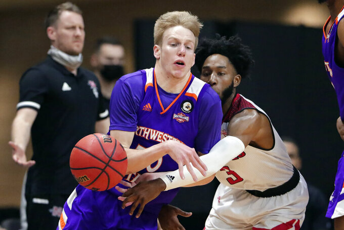Northwestern State guard Trenton Massner, left, has the ball knocked away by Nicholls State guard Kevin Johnson (3) during the first half of an NCAA college basketball game in the Southland Conference men's tournament semifinals Friday, March 12, 2021, in Katy, Texas. (AP Photo/Michael Wyke)