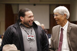 Makah Tribal Council Member Patrick DePoe, left, talks with Marine Mammal Commission Commissioner Michael F. Tillman before a federal court hearing to help determine whether DePoe's small American Indian tribe can once again hunt whales, Thursday, Nov. 14, 2019, in Seattle. The symbol DePoe wears is from the tribe's flag, and includes bird and whale symbols. The Makah Tribe, from the northwest corner of Washington state, conducted its last legal hunt in 1999, when its crew harpooned a gray whale from a cedar canoe. (AP Photo/Elaine Thompson)
