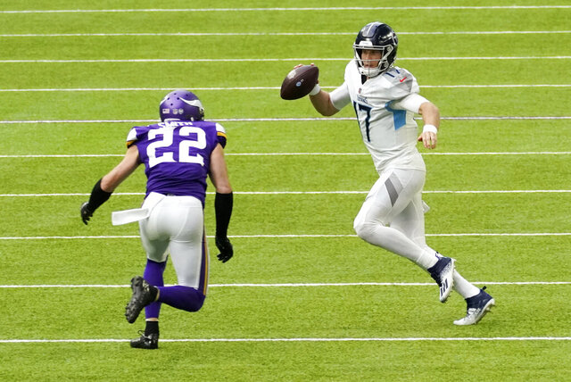 Tennessee Titans quarterback Ryan Tannehill (17) runs from Minnesota Vikings strong safety Harrison Smith (22) during the second half of an NFL football game, Sunday, Sept. 27, 2020, in Minneapolis. (AP Photo/Jim Mone)