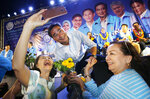 In this March 18, 2019, photo, a supporter takes a selfie with the leader of Thailand's Democrat Party and candidate for prime minister Abhisit Vejjajiva, center, during an election campaign in Bangkok, Thailand. More than 70 parties are contesting Sunday's general election in Thailand, the first since a military coup nearly five years ago. (AP Photo/Sakchai Lalit)