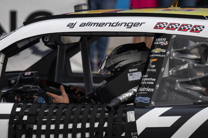 NASCAR Xfinity Series driver AJ Allmendinger (16) removes the steering wheel from his car in victory lane after the NASCAR Xfinity auto racing race at the Charlotte Motor Speedway Saturday, Oct. 9, 2021, in Concord, N.C. (AP Photo/Matt Kelley)