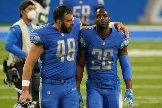 Detroit Lions long snapper Don Muhlbach (48) and strong safety Duron Harmon (26) walk off the field after an NFL football game against the Green Bay Packers, Sunday, Dec. 13, 2020, in Detroit. (AP Photo/Paul Sancya)