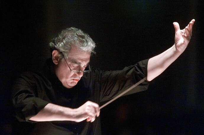 FILE - In this Saturday, Jan. 27, 2001, file photo, Placido Domingo directs the Washington Opera Orchestra and Chorus during a rehearsal of Verdi's Requiem at Washington's Constitution Hall. Nine women in the opera world have told The Associated Press that they were sexually harassed by Domingo in encounters that took place over three decades, at venues that included the Washington Opera, the Los Angeles Opera and other opera companies. (AP Photo/Richard Drew, File)