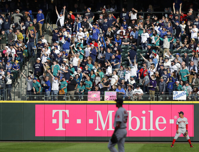 Fans in the stands cheer as they watch a two-run home run by Seattle Mariners' Tim Beckham during the third inning of a baseball game against the Boston Red Sox, Thursday, March 28, 2019, in Seattle. The homer was Beckham's second of the day. (AP Photo/Ted S. Warren)