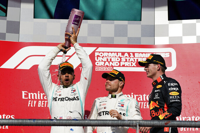 Mercedes driver Lewis Hamilton, left, of Britain, celebrates as Mercedes driver Valtteri Bottas, middle, of Finland, and Red Bull driver Max Verstappen, of the Netherlands, watch following the Formula One U.S. Grand Prix auto race at the Circuit of the Americas, Sunday, Nov. 3, 2019, in Austin, Texas. (AP Photo/Chuck Burton)