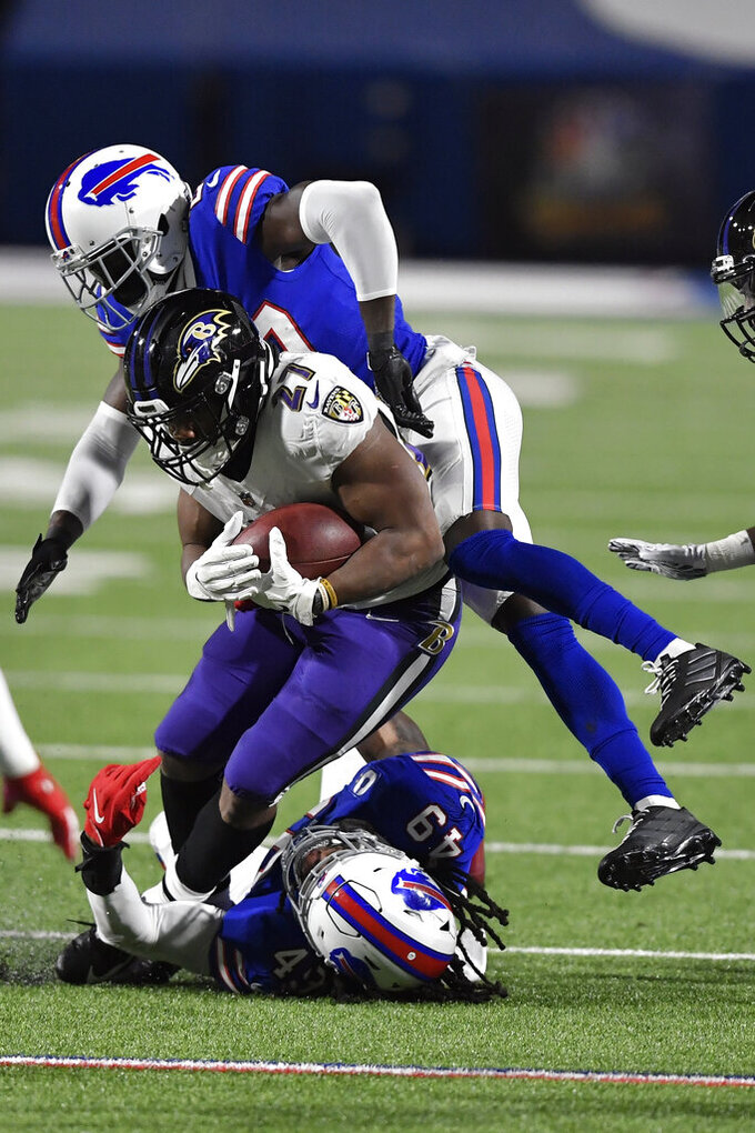 Baltimore Ravens' J.K. Dobbins (27) is tackled by Buffalo Bills' Tremaine Edmunds (49) and Micah Hyde during the first half of an NFL divisional round football game Saturday, Jan. 16, 2021, in Orchard Park, N.Y. (AP Photo/Adrian Kraus)