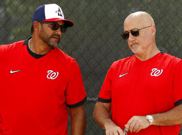 FILE - In this Feb. 17, 2020, file photo, Washington Nationals manager Dave Martinez, left, talks with general manager Mike Rizzo during spring training baseball practice in West Palm Beach, Fla. Nationals general manager Mike Rizzo says his top offseason priority is adding a middle-of-the-order hitter.  (AP Photo/Jeff Roberson, File)