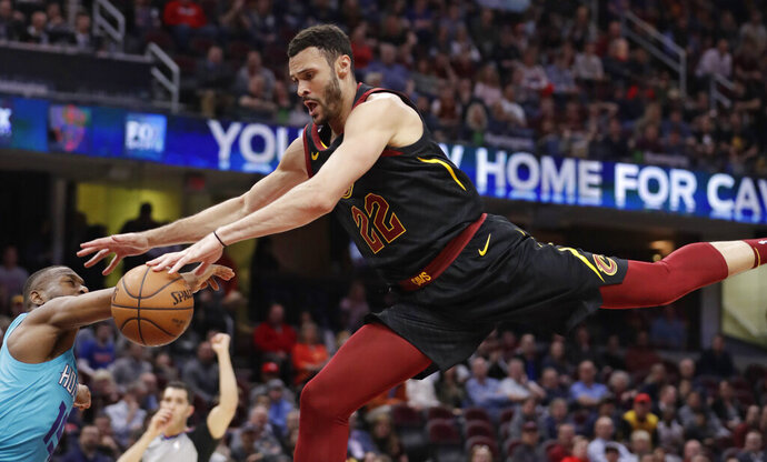 Cleveland Cavaliers' Larry Nance Jr., right, drives to the basket against Charlotte Hornets' Kemba Walker in the first half of an NBA basketball game, Tuesday, April 9, 2019, in Cleveland. Walker was called for a foul. (AP Photo/Tony Dejak)