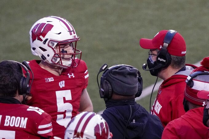 Wisconsin head coach Paul Chryst talks to quarterback Graham Mertz during the first half of an NCAA college football game against Indiana Saturday, Dec. 5, 2020, in Madison, Wis. (AP Photo/Morry Gash)