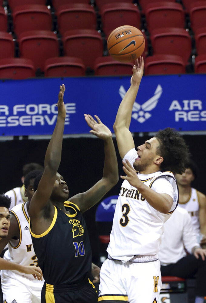 Wyoming guard Kwane Marble II (3) shoots as San Jose State guard Omari Moore (10) defends during the second half of an NCAA college basketball game in the first round of the Mountain West Conference men's tournament Wednesday, March 10, 2021, in Las Vegas. (AP Photo/Isaac Brekken)