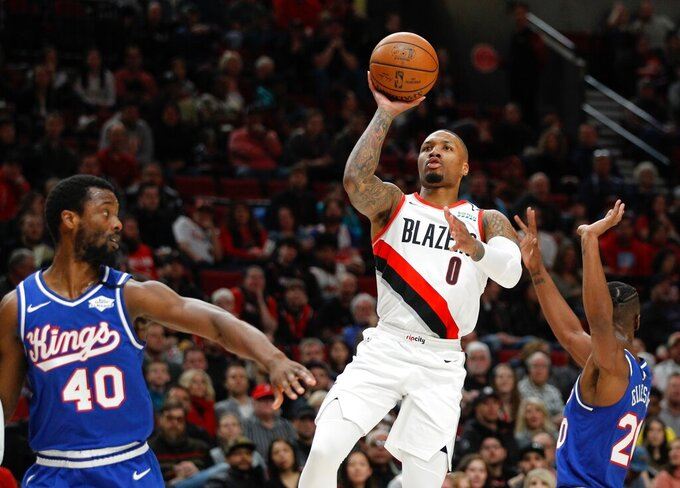 FILE - In this Saturday, March 7, 2020, file photo, Portland Trail Blazers guard Damian Lillard, center, shoots as Sacramento Kings forward Harrison Barnes, left, and forward Harry Giles III, right, defend during the first half of an NBA basketball game in Portland, Ore. Lillard says he will spend most of his downtime working on recording music while inside the NBA bubble. (AP Photo/Steve Dipaola, File)