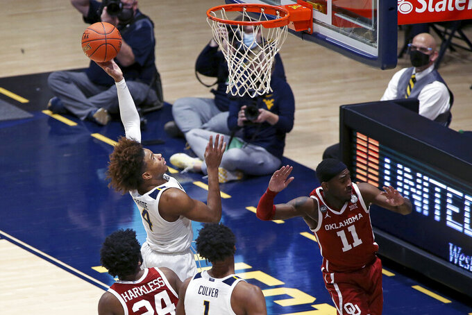 West Virginia guard Miles McBride (4) shoots past Oklahoma guard Elijah Harkless (24) during  overtime of an NCAA college basketball game Saturday, Feb. 13, 2021, in Morgantown, W.Va. (AP Photo/Kathleen Batten)