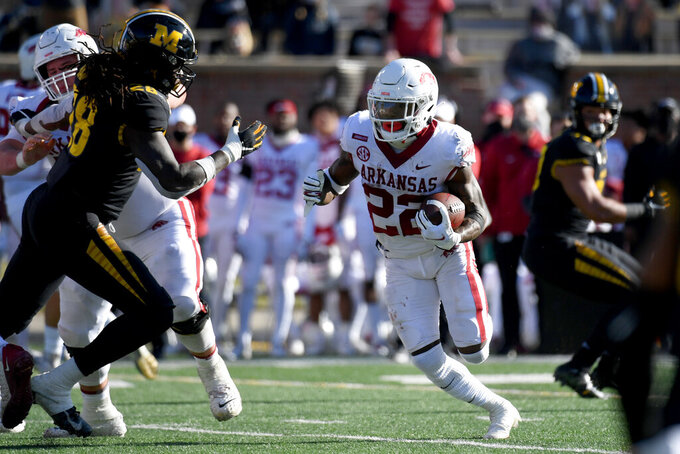 Arkansas running back Trelon Smith (22) scores on a touchdown run past Missouri linebacker Jatorian Hansford, left, during the second half of an NCAA college football game Saturday, Dec. 5, 2020, in Columbia, Mo. (AP Photo/L.G. Patterson)