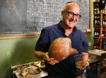 Prof. Aren Maeir, from Bar Ilan University, holds an ancient jar and a glass of beer during a press conference in Jerusalem, Wednesday, May 22, 2019. Israeli researchers celebrated Wednesday a long-brewing project of making beer and mead using yeasts extracted from ancient clay vessels -- some over 5,000 years old. Archaeologists and microbiologists teamed up to study yeast colonies found in microscopic pores in ancient pottery fragments. (AP Photo/Sebastian Scheiner)