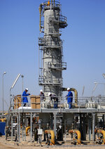 FILE - In this Tuesday, Feb. 21, 2017 file photo, oil laborers work at West Qurna oil field near the city of Basra, Iraq. An Iraqi oil official says employees of energy giant Exxon Mobil have started evacuating an oil field in the southern province of Basra, amid rising tensions between the United States and Iran. The first group left two days ago and another batch left early Saturday May 18, 2019. (AP Photo/Nabil al-Jurani, File)