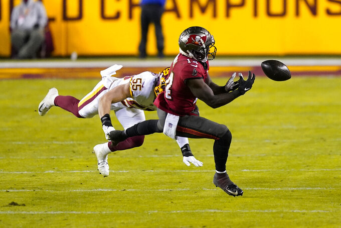Tampa Bay Buccaneers wide receiver Chris Godwin (14) drops a pass as he goes up against Washington Football Team outside linebacker Cole Holcomb (55) during the second half of an NFL wild-card playoff football game, Saturday, Jan. 9, 2021, in Landover, Md. (AP Photo/Andrew Harnik)