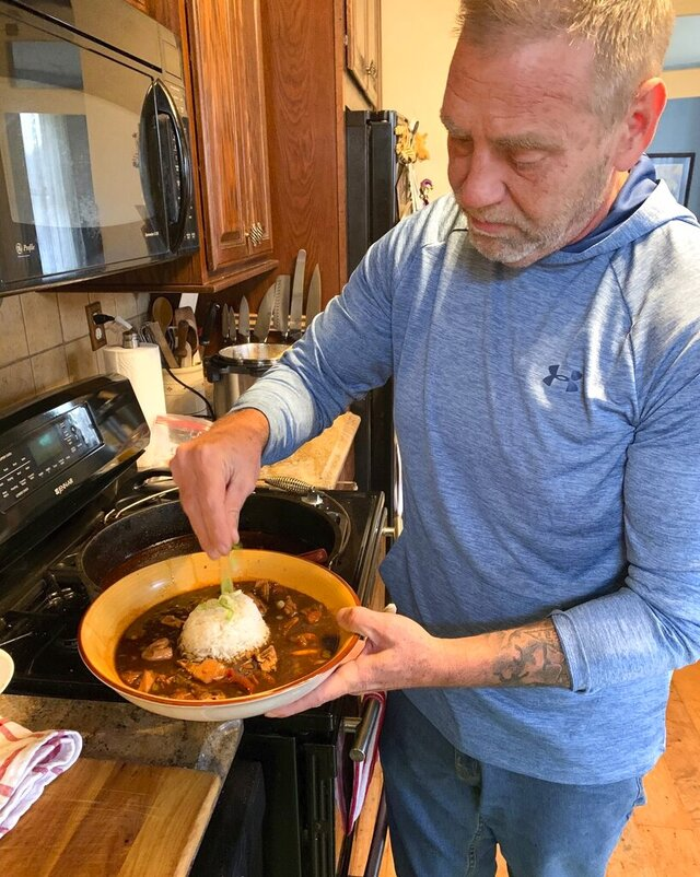 Kevin Lipps adds some scallions to the top of his finished gumbo with rice at his home on Feb. 9, 2020 in Frederick, Md.   Lipps lived and ran a restaurant outside of New Orleans for two years where he learned how to make a proper gumbo.  (Crystal Schelle/The Frederick News-Post via AP)
