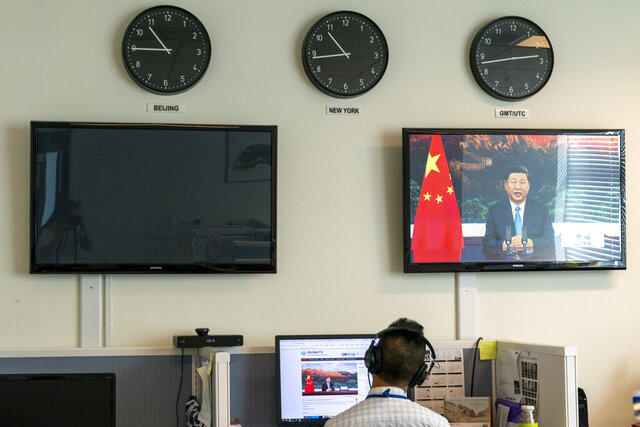 A reporter with the Xinhua Press Agency watches as President Xi Jinping is seen on a video screen remotely addressing the 75th session of the United Nations General Assembly, Tuesday, Sept. 22, 2020, at U.N. headquarters. This year's annual gathering of world leaders at U.N. headquarters will be almost entirely
