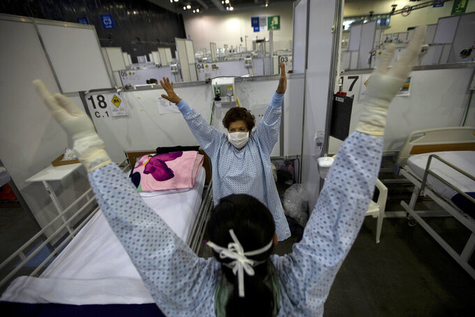 FILE - In this March 11, 2021 file photo, directed by a nurse, a COVID-19 patient, back center, stretches her arms as part of a fitness program in a field hospital built inside the Citibanamex convention center in Mexico City. Mexico's unwillingness to spend money, do more testing, change course or react to new scientific evidence contributed to the country being one of the worst hit by the coronavirus pandemic, according to a report released the third week of April, by the University of California, San Francisco. (AP Photo/Fernando Llano, File)