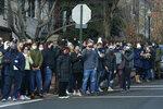 People gather to watch as President Joe Biden's motorcade departs Holy Trinity Catholic Church, Sunday, Jan. 24, 2021, in the Georgetown neighborhood of Washington. (AP Photo/Patrick Semansky)