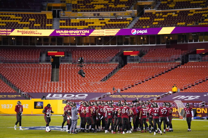 Members of the Tampa Bay Buccaneers gather in the field before the start of an NFL wild-card playoff football game against the Washington Football Team, Saturday, Jan. 9, 2021, in Landover, Md. (AP Photo/Andrew Harnik)
