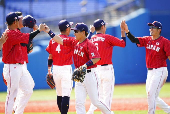 Japan's Masataka Yoshida, center, celebrates with teammates after Japan won a baseball game against Mexico at Yokohama Baseball Stadium during the 2020 Summer Olympics, Saturday, July 31, 2021, in Yokohama, Japan. (AP Photo/Matt Slocum)
