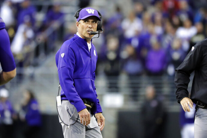 Washington head coach Chris Petersen talks on his headset during the second half of an NCAA college football game against Hawaii, Saturday, Sept. 14, 2019, in Seattle. Washington won 52-20. (AP Photo/Ted S. Warren)