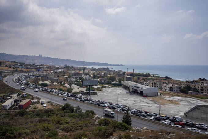 A general view of a petrol station on the main highway that links the Capital Beirut to south Lebanon, as cars come from every direction to try and fill their tanks with gasoline, in the coastal town of Jiyeh, south of Beirut, Lebanon, Friday, Sept. 3, 2021.  Lebanon is mired in a devastating economic and financial crisis, the worst in its modern history. A result of this has been crippling power cuts and severe shortages in gasoline and diesel that have been blamed on smuggling, hoarding and the cash-strapped government's inability to secure deliveries of oil products. (AP Photo/ Hassan Ammar)