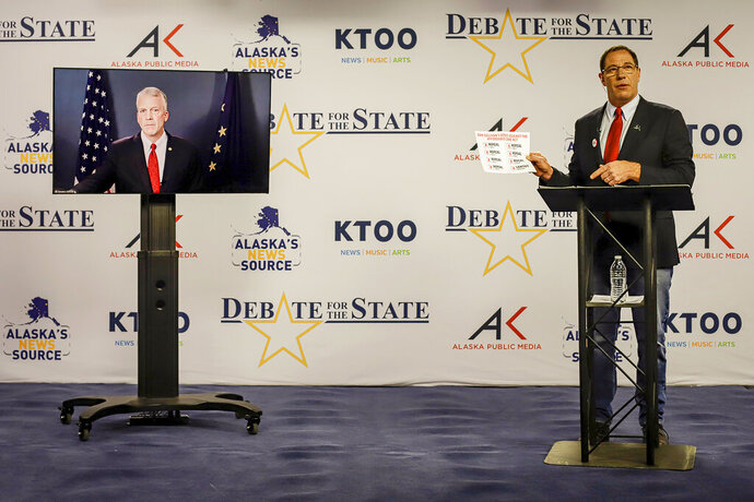 Al Gross, right, an independent in Alaska's U.S. Senate race, holds a document during a debate with Republican U.S. Sen. Dan Sullivan on Friday, Oct. 23, 2020, in Anchorage, Alaska. Sullivan participated remotely, as the Senate prepares to vote on President Donald Trump's Supreme Court nominee in Washington. (Jeff Chen/Alaska Public Media via AP, Pool)