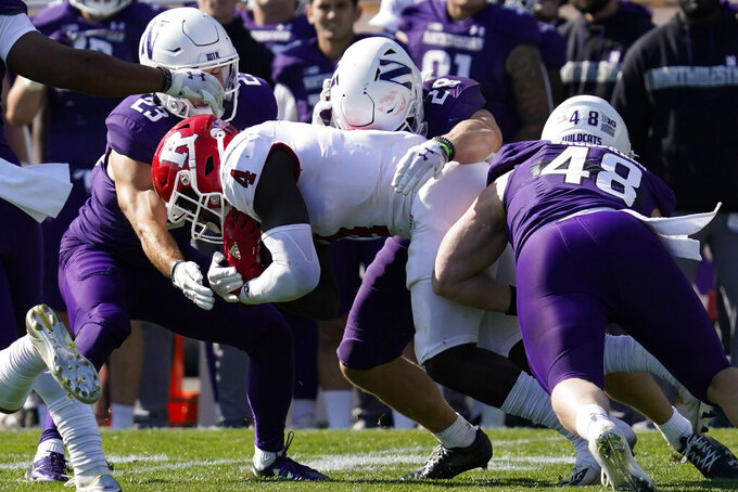 Rutgers running back Aaron Young (4) is tackled by Northwestern's Raymond Niro III (23), linebacker Chris Bergin (28) and linebacker Owen Berginduring (48) during the second half of an NCAA college football game in Evanston, Ill., Saturday, Oct. 16, 2021. Northwestern won 21-7. (AP Photo/Nam Y. Huh)